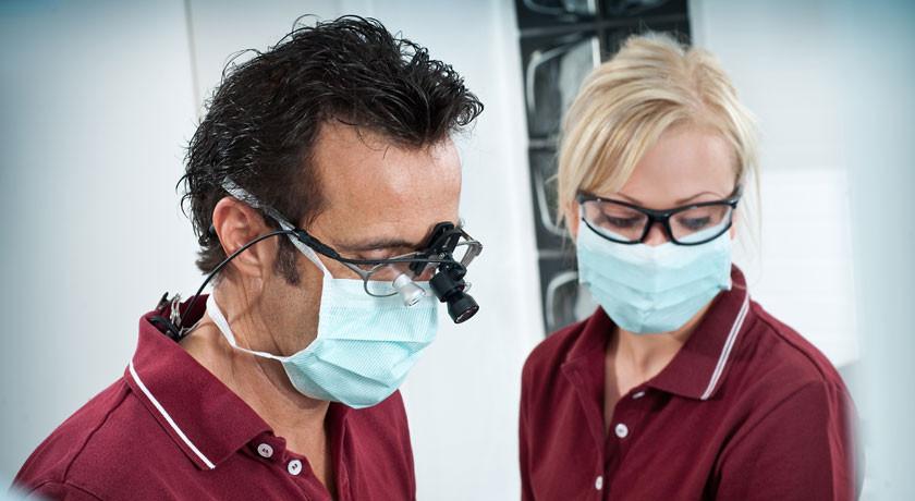 Zahnarzt Dr. T. Wingendorf arbeitet mit Lupenbrille
