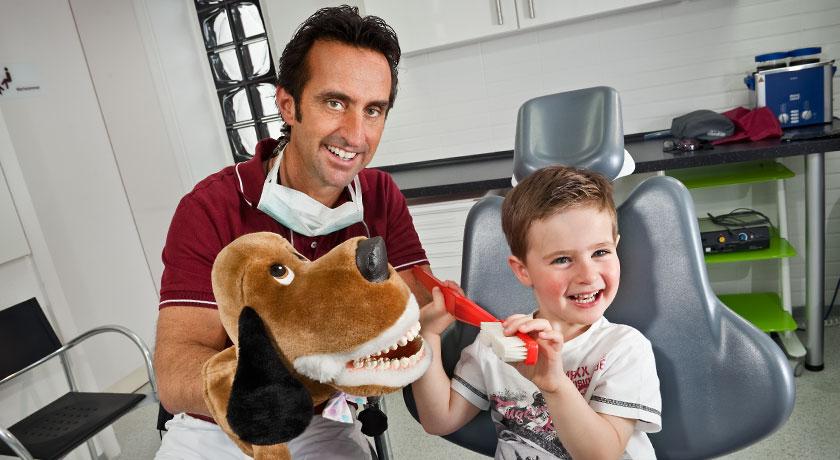 Zahnarzt Dr. T. Wingendorf übt mit Kind Zahnpflege an Hundepuppe - Kinderzahnheilkunde. Foto © Dietrich Hackenberg